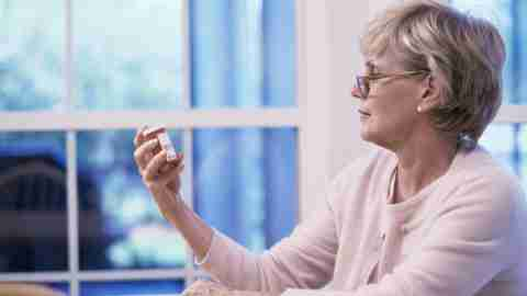 Woman is reading her bottle of pills and taking ADHD treatment after learning more about it.