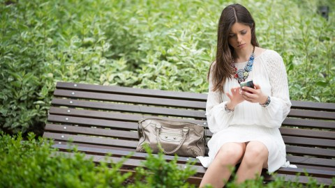 A woman with ADHD checks her cell phone will sitting alone lonely on a park bench