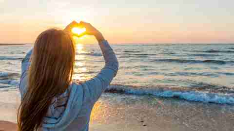 A woman with ADHD stands by the ocean and makes a heart with her hands.