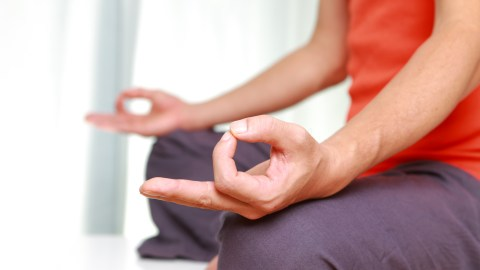 A man sits with his hands in lotus position, part of his ADHD stress management plan.