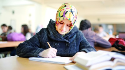 Student with ADHD and executive function disorder reading book in library