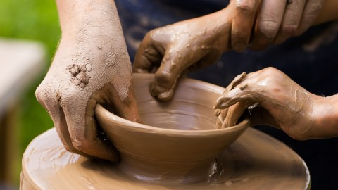 A potters hands guiding a child's hands to help him to work with the ceramic wheel because they both have ADHD