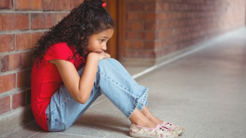 A girl sits in the hallway by herself. She has withdrawn socially because of Minecraft addiction.