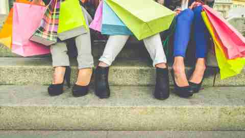 A group of women with shopping bags. One cleaning tip to reduce clutter is to stop buying new things.