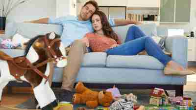 A couple with ADHD sleeps on the couch in the middle of a messy living room.