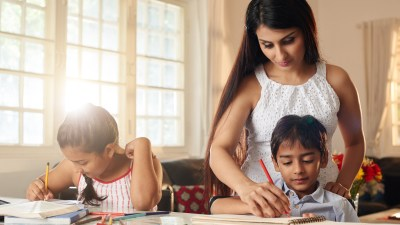 A mother helps her children work through difficult problems one step at a time, a good strategy to avoid homework stress.