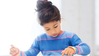 A girl uses a tablet with apps for kids with ADHD.
