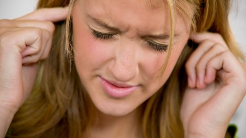 A child with Sensory Processing Disorder plugs her sensitive ears because the sound is too loud.