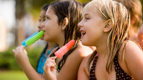A girl with ADHD eats a popsicle with her friends