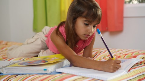A young girl with ADHD practicing writing strategies while lying on her bed