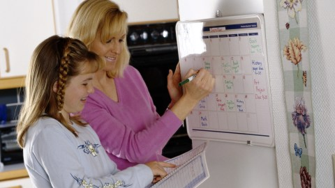 A mother and daughter make a calendar of upcoming assignments together, which is a must to arrange before school starts.