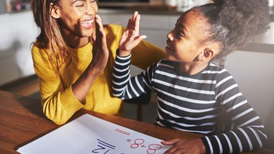 A mom gives her daughter a high five. Praise is one of her ADHD parenting strategies.