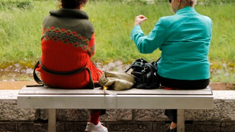 A woman with ADHD sits on a bench and talks to another woman