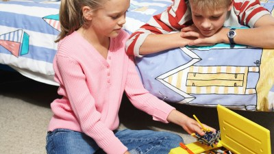 A boy and girl with ADHD pick up their toys as part of their daily routine.