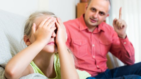 A child covers her face with her hands while her father lectures her about anger management.