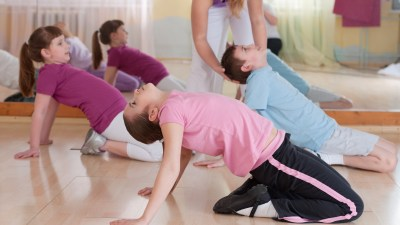 A group of children do yoga together as part of anger management for kids.