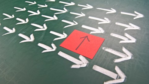 One arrow points a different direction from other arrows, a metaphor for changing a daily routine