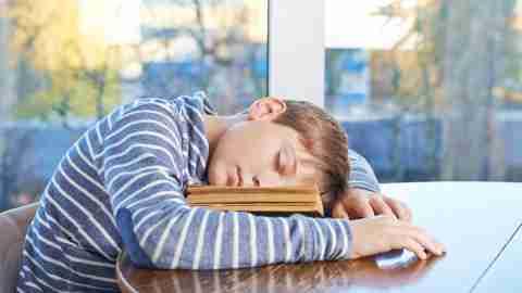 Boy with ADHD asleep on book