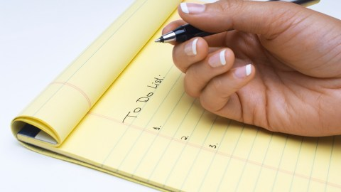 A woman with ADHD makes a to-do list of goals