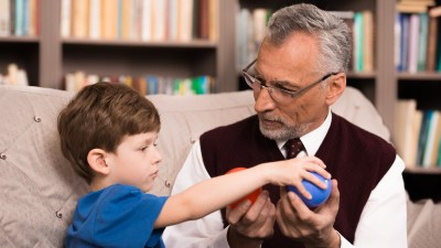 A boy works with an occupational therapist to manage symptoms of sensory processing disorder