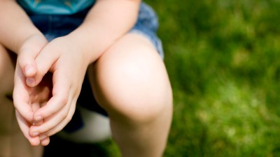 A child with sensory processing disorder sits on a soccer ball