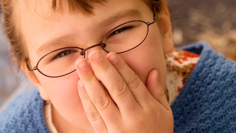 A girl with ADHD covers her mouth after telling a lie
