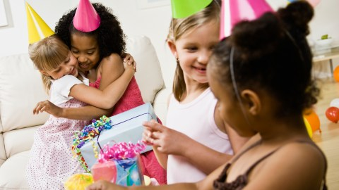 Two girls with ADHD hug at a birthday party