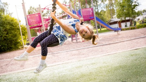 Girl with ADHD on a tire swing is called just a little hyper.
