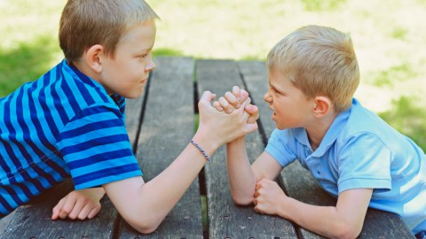 Boys arm wrestling. Some say ADHD behavior is bad parenting.