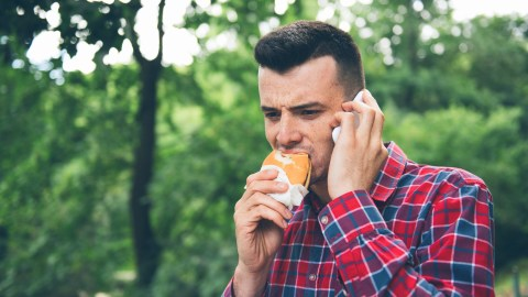 A man with ADHD eats a burger while talking on the phone