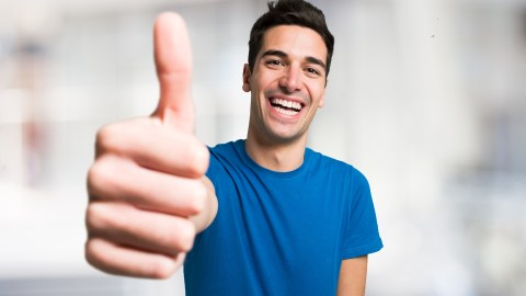 A happy man with ADHD gives a thumbs up