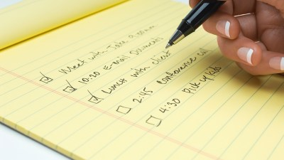A woman with ADHD writes a to-do list for the day