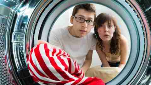 Parents examine a washing machine, after their daughter managed to get stuck in it.