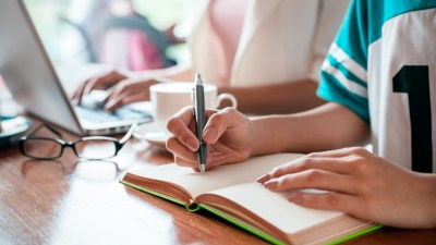 A child's hands writing in a notebook while learning how to study effectively with ADHD
