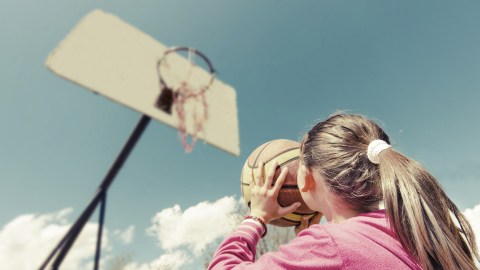 A young girl playing basketball outside, since exercise is a great way for kids with ADHD to learn how to study