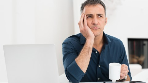 A man sits in front of a laptop with a coffee cup and wonders how to succeed with ADHD at work.