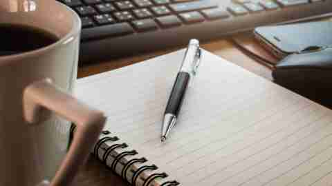"""A close-up of a cup of coffee and notebook on a desk, set down while a person wonders, """"Should I tell my boss I have ADD?"""""""