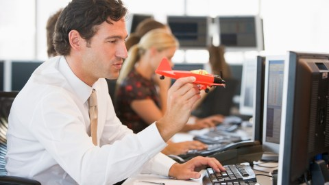 A man with inattentive ADHD plays with a model airplane at work because he is easily distracted.