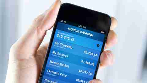 Mobile banking app on a cell phone screen, held by someone learning how to save money
