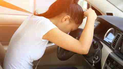 A woman with ADHD and dysthymia rests her head on the steering wheel in despair.