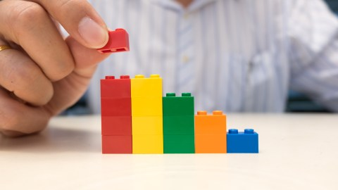 A man puts together a set of blocks to demonstrate some smart productivity tips.