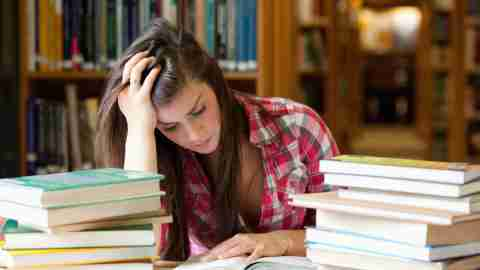 A girl looks stressed in the library where she reads books about the different types of learning disabilities.