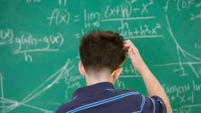A boy stands in front of a chalk board and scratches his head, confused about the different types of learning disabilities
