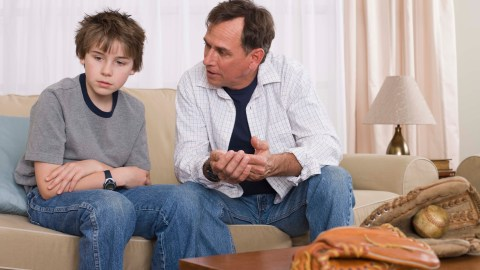 A father talks to his angry child with ADHD on the couch.