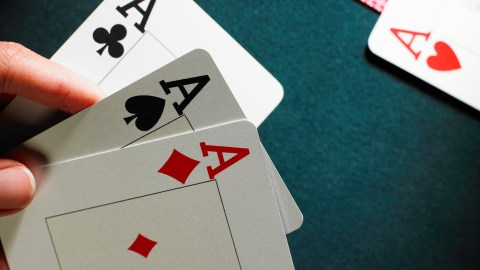 A hand of cards with three aces.