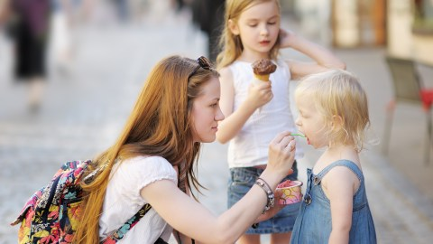 A mom with ADHD feeding her young child frozen yogurt