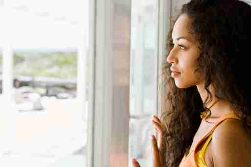 A woman with analysis paralysis staring out the window