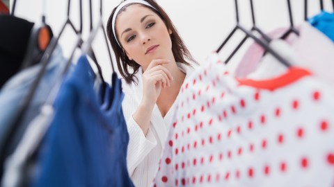 Woman looking at clothes and trying to overcome analysis paralysis