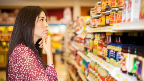 A woman with analysis paralysis trying to decide what to buy at the store