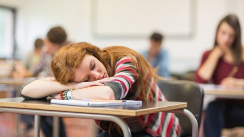 A girl dozes off in class, showing symptoms of inattentive ADHD.